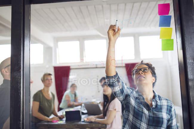 Lluvia de ideas de compañeros de trabajo en la oficina - foto de stock