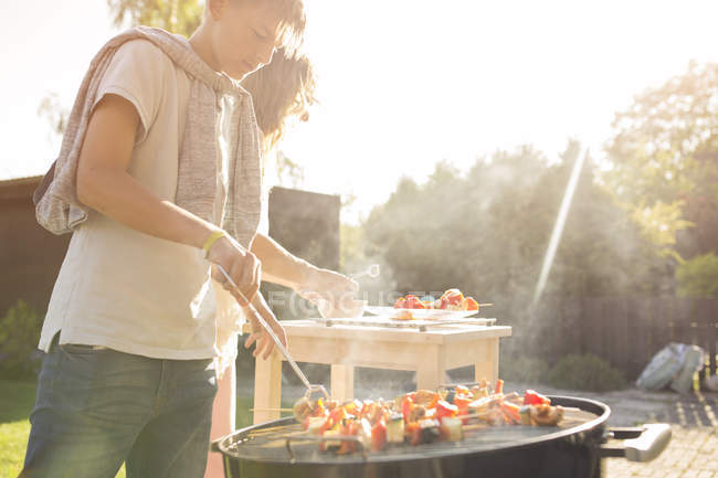 Mature woman and teenager barbecuing at garden party — Stock Photo