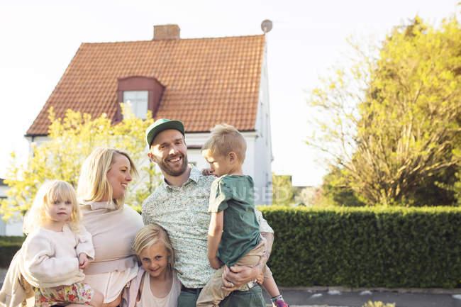 Família com três filhos em pé em frente à casa suburbana — Fotografia de Stock