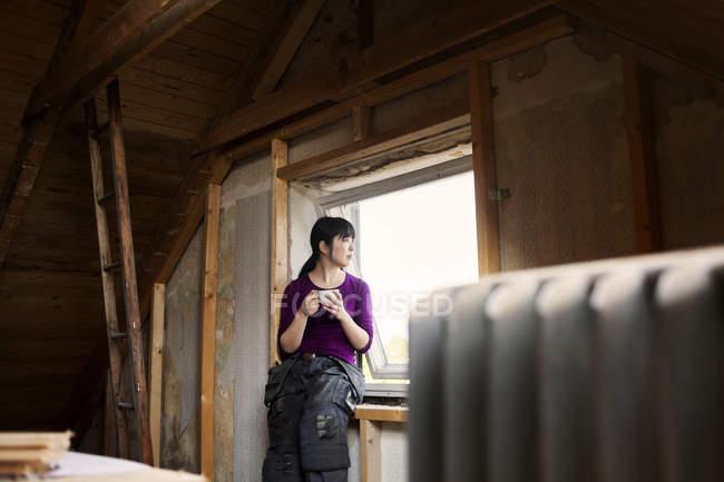 Frau sitzt auf der Fensterbank — Stockfoto