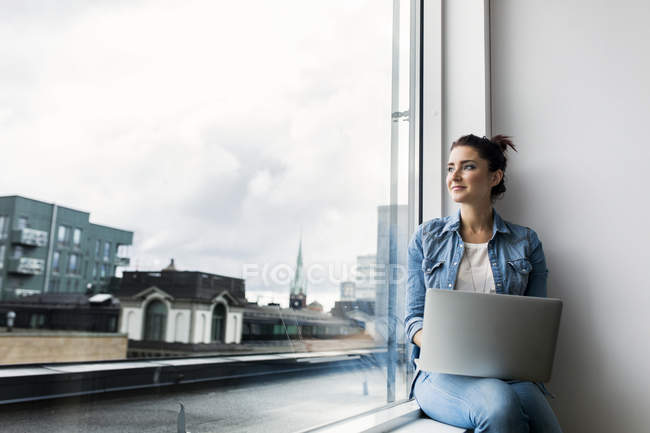 Woman with laptop looking through window in office — Stock Photo