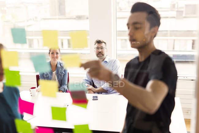 Коллеги рассматривают клейкие заметки во время деловой встречи — стоковое фото