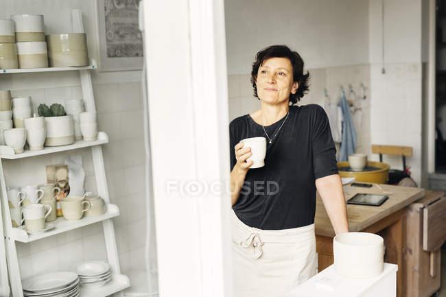 Tasse café tenue potter féminin — Photo de stock