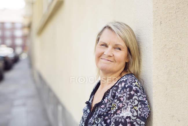 Женщина опирается на стену здания — стоковое фото