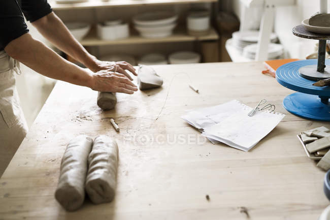 Female potter rolling clay — Stock Photo