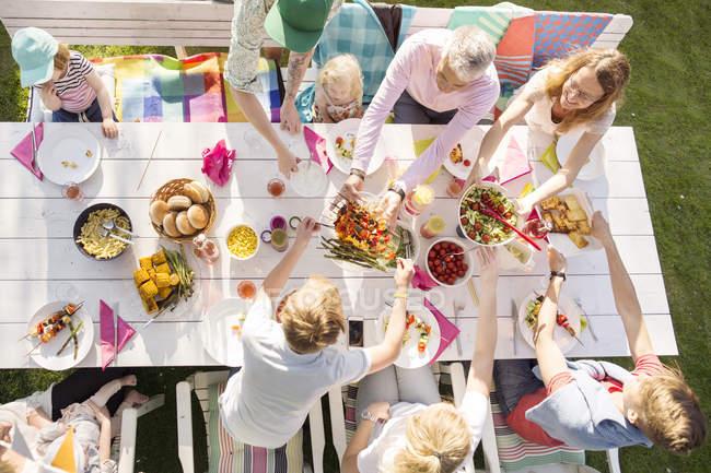 Вид сверху на семью, сидящую за обеденным столом на садовом празднике в заднем дворе — стоковое фото