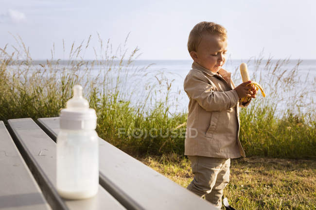 Toddler boy holding banana — Stock Photo