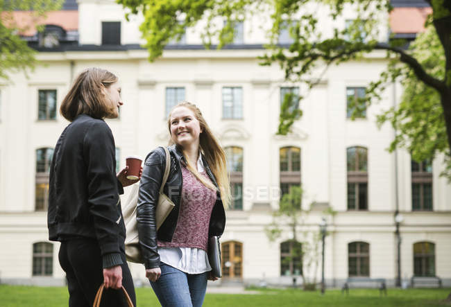 Two students talking in university yard with cup of coffee — Stock Photo