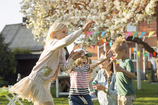 Женщина и дети раздувают пузыри в саду — стоковое фото