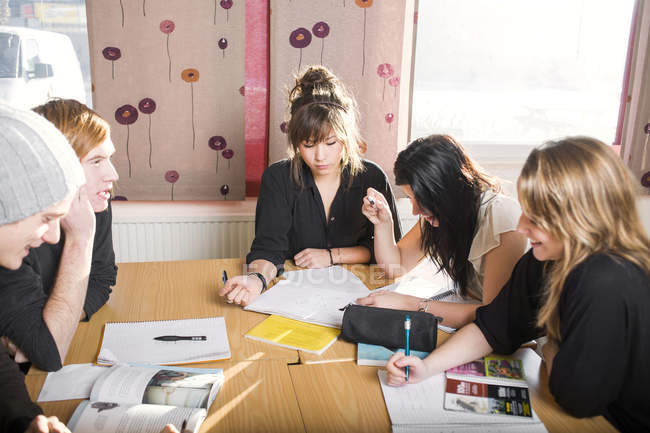 High angle view of students studying at table in common room — Stock Photo