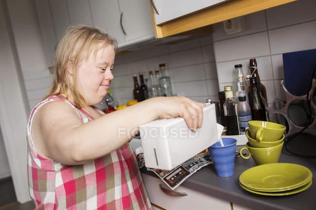 Frau mit Down-Syndrom Gießen Milch Becher in Küche — Stockfoto