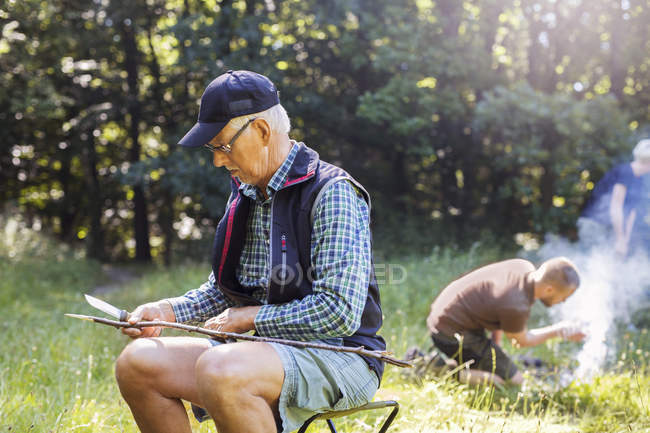 Man sharpening stick at forest — Stock Photo