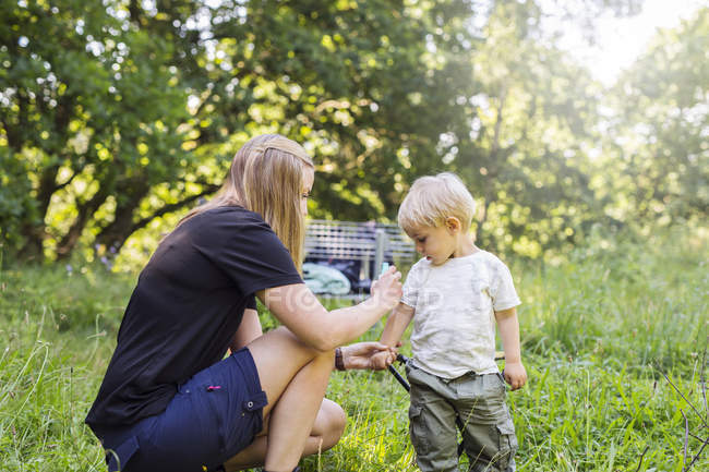Mother spraying son (2-3) with insect repellant — Stock Photo