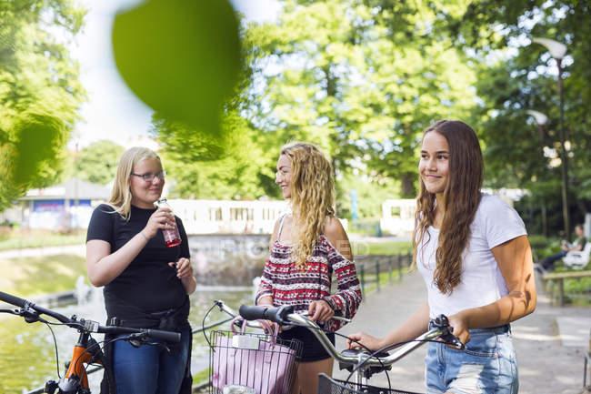Adolescentes com bicicletas (14-15) andando no parque — Fotografia de Stock