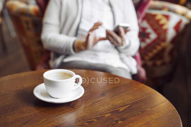 Чашки кави порожній і жінка, що використання мобільного телефону у фоновому режимі — стокове фото