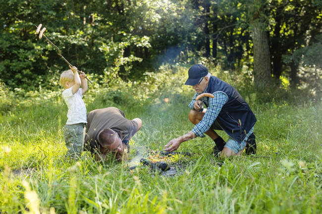 Family preparing food on camp fire — Stock Photo