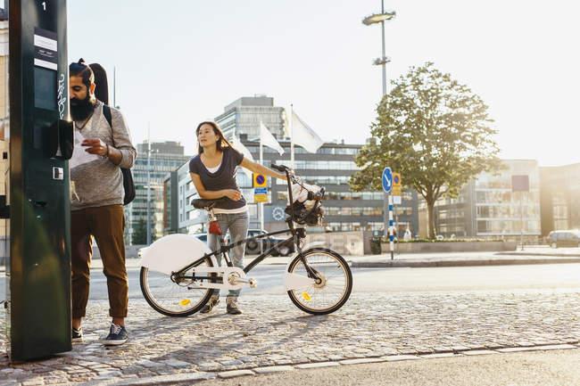 Personas que alquilan bicicletas en la estación de alquiler - foto de stock