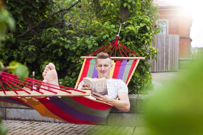 Uomo che legge il libro sul hammock durante il giorno — Foto stock