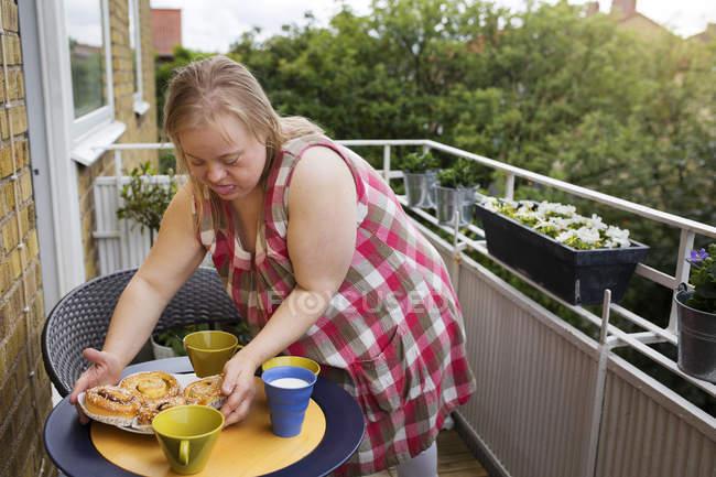 Frau mit Down-Syndrom bereitet Imbiss auf Balkon zu — Stockfoto