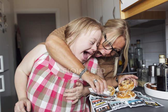 Mutter und Tochter mit Down-Syndrom essen Teig in Küche — Stockfoto