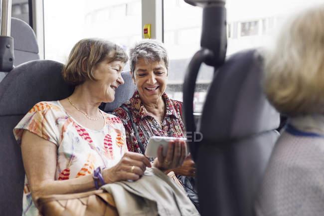 Due donne sorridenti che guardano il cellulare in autobus — Foto stock