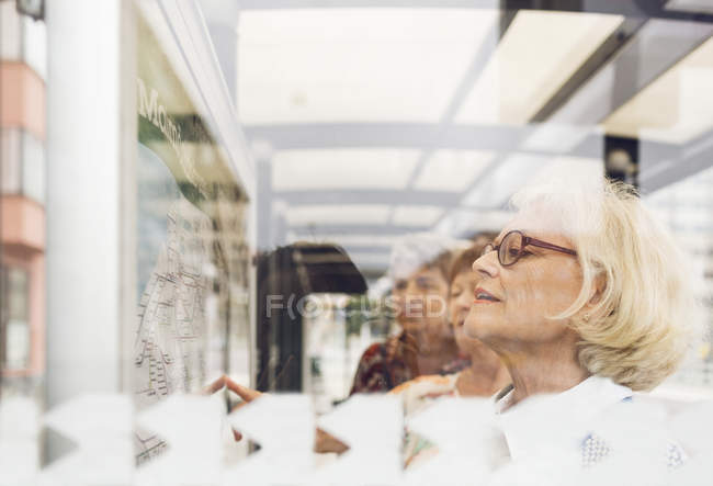 Tre donne che guardano la mappa dei trasporti pubblici — Foto stock