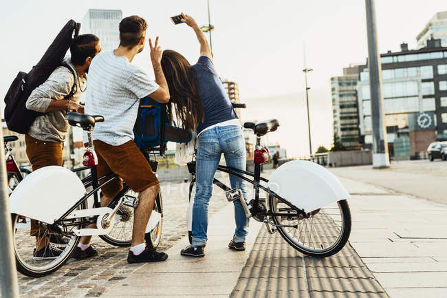 Três pessoas com bicicletas fotografando-se na cidade — Fotografia de Stock