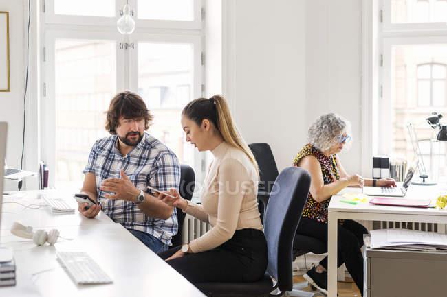 Editores con teléfono en la oficina - foto de stock
