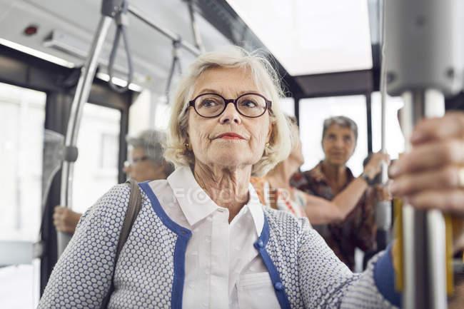 Donna anziana che tiene corrimano in autobus — Foto stock