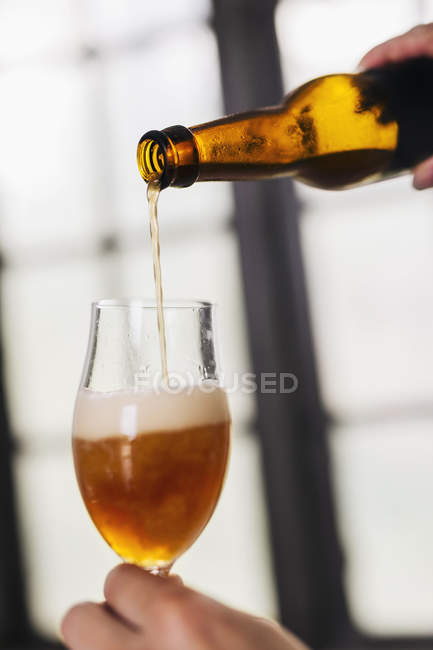 Close-up of brewery worker pouring beer from bottle into glass — Stock Photo