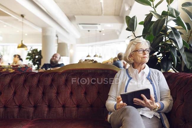Старшие женщины с цифровой планшет, сидя на диване и глядя — стоковое фото