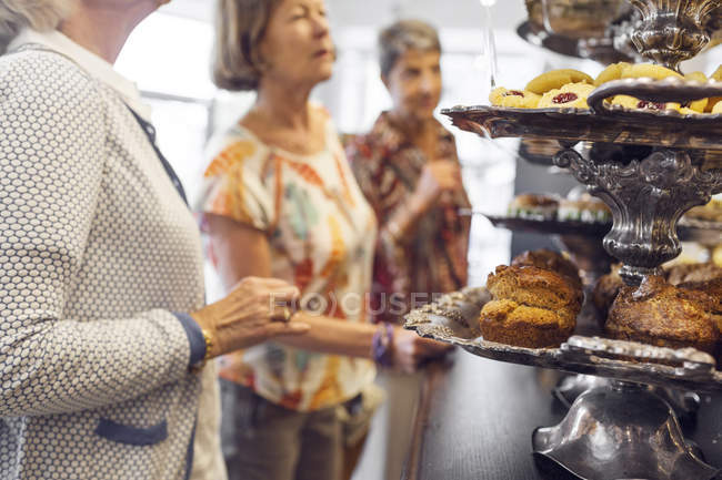 Three women choosing dessert in cafe — Stock Photo