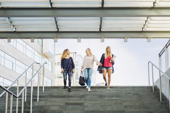 Tres jóvenes caminando por escaleras - foto de stock