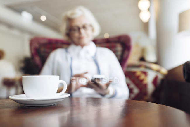 Coffee cup on table and senior woman using mobile phone during coffee break in cafe — Stock Photo