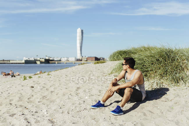 Young man sitting on beach — Stock Photo