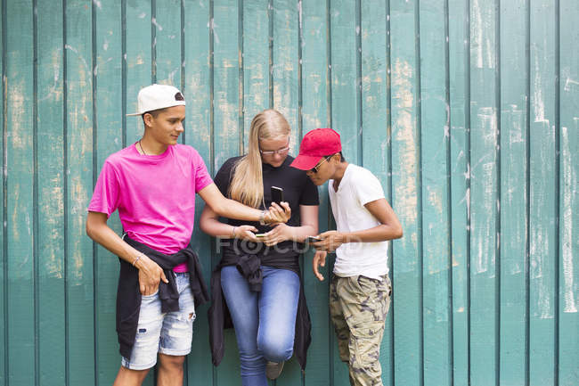 Teenage girl and teenage boys (14-15) looking at smart phone — Stock Photo