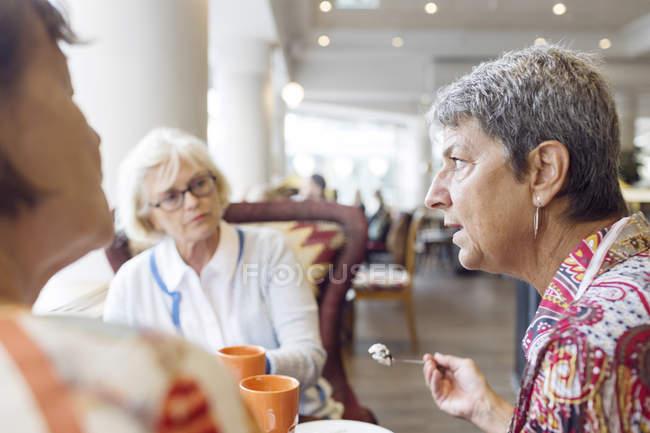 Três mulheres que tomam café no café — Fotografia de Stock