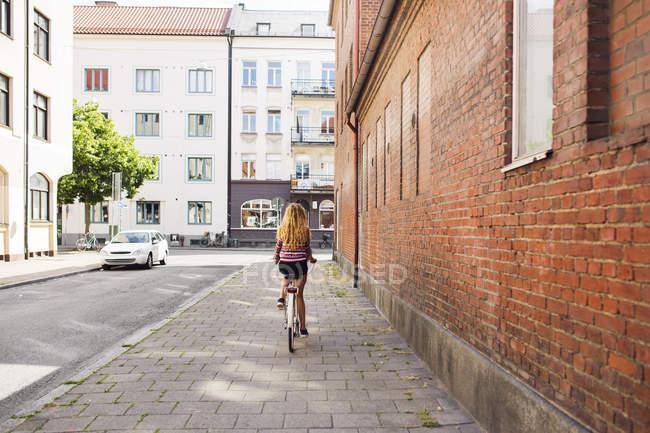 Adolescente (14-15) à vélo en ville — Photo de stock