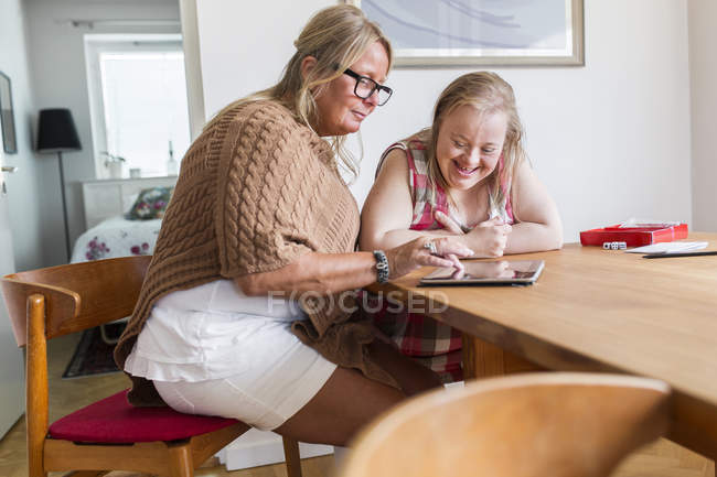 Mother and daughter with down syndrome using digital tablet — Stock Photo