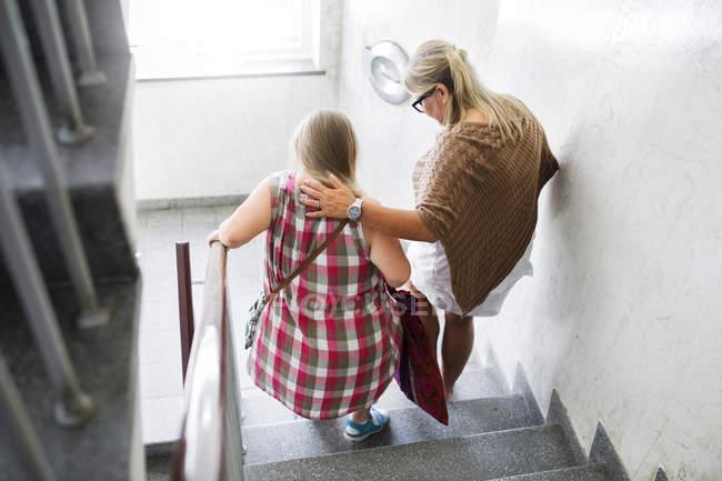 Мать и дочь с синдромом Дауна, пешком вниз по лестнице — стоковое фото