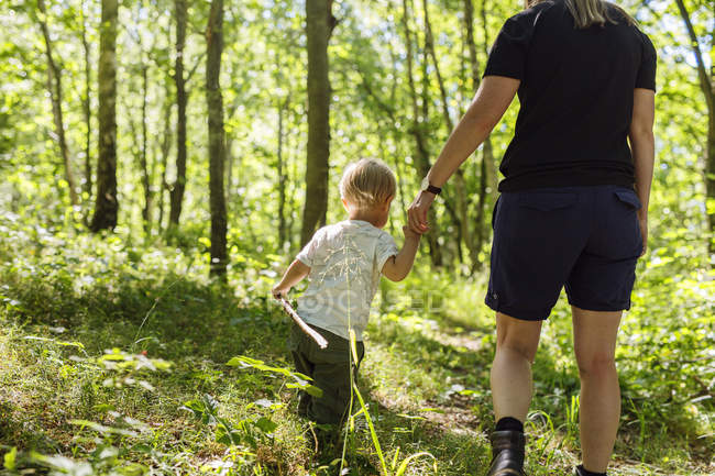 Boy (2-3) walking in forest with mother — Stock Photo
