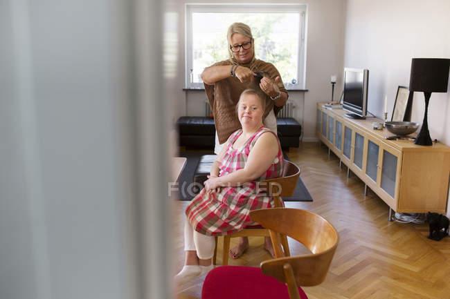 Cepillado cabello de hijas madre - foto de stock