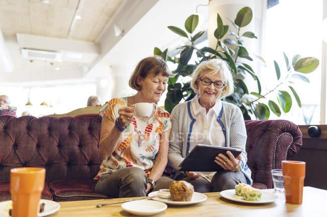 Due donne che utilizzano tablet digitale in caffè — Foto stock
