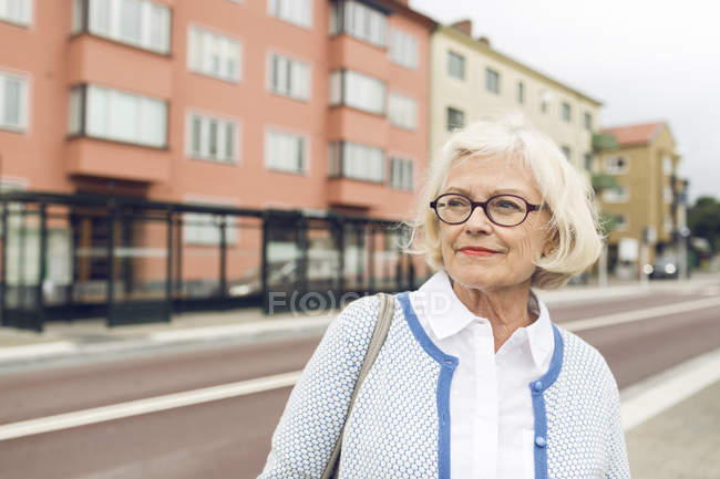 Femme debout à côté de l'arrêt de bus et regardant loin — Photo de stock
