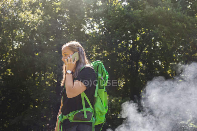 Young woman talking on phone in meadow — Stock Photo