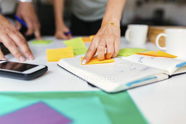 Colegas de trabalho usando o bloco de notas durante a discussão sobre o projeto — Fotografia de Stock