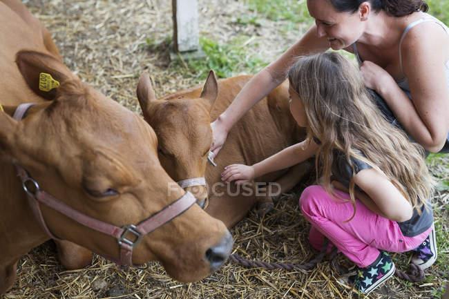Madre con figlia (4-5) vitello accarezzando — Foto stock