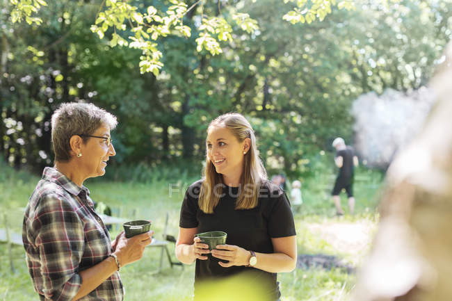 Women holding cups and standing in meadow — Stock Photo