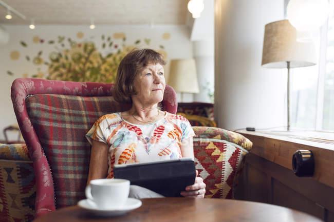Старшие женщины глядя через окно во время перерыва на кофе в кафе — стоковое фото