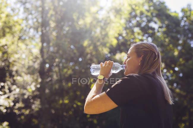 Femme eau potable à la forêt pendant la journée — Photo de stock